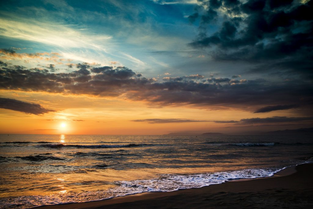The sun sets over the ocean representing when our dear ones cross over. A psychic medium reading can be a powerful way to heal and overcome grief and pain.